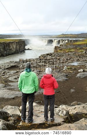 Hikers looking at Iceland nature by waterfall Selfoss waterfall. People enjoying view of famous Icelandic tourist attraction. Hiking couple taking break by Selfoss in Vatnajokull national park.