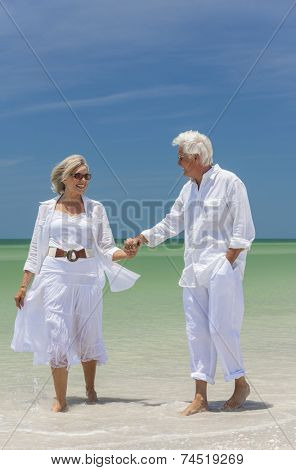 Happy senior man and woman couple walking, laughing and holding hands on a deserted tropical beach with bright clear blue sky