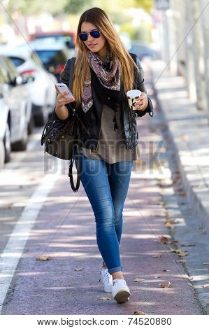 Portrait Of Beautiful Girl Drinking Coffee And Using Her Mobile Phone In City.