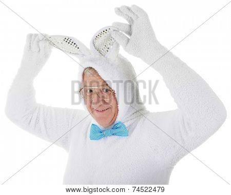 Close-up image of a senior adult man in a full-body white bunny outfit happily holding his ears up.  On a white background.