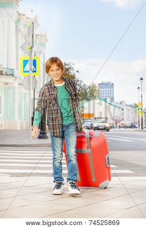 Smiling boy holds red luggage and walks on street