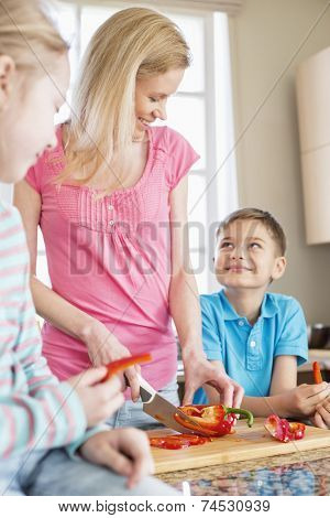 Happy woman chopping red bell pepper while standing with children in kitchen