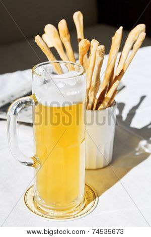 Mug Of Beer And Bread Sticks On Table