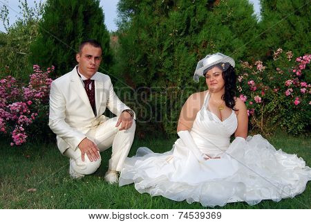 Young bride and groom couple posing outside