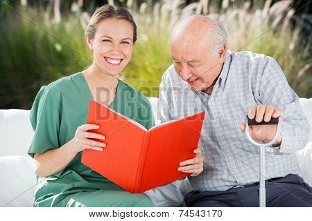 Portrait of happy female nurse reading book for senior man at nursing home