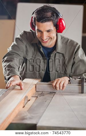 Happy young carpenter cutting wooden plank with tablesaw in workshop