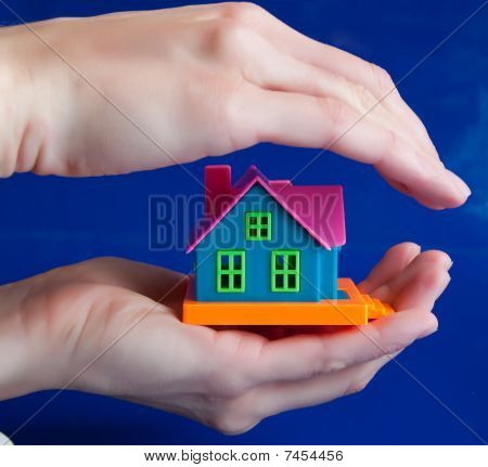 Toy House In Human Hands - A Symbol Of Protection