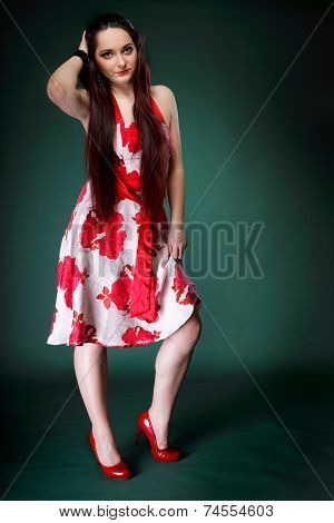 Young Woman In Summer Flowery Dress On Green