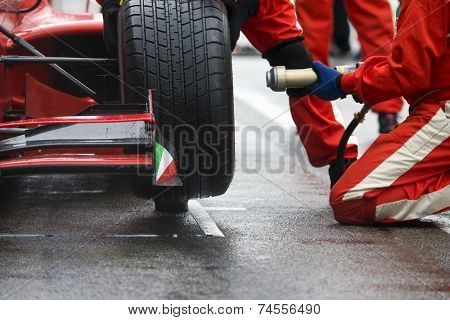 Professional racing team at work during a pitstop of a race car in the pitslane during a car race.
