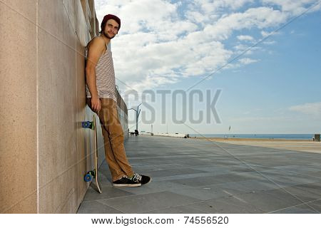Young, carefree, skateboarder guy, leaning against a granite wall at a beach with his skateboard next to him