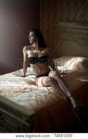 Beautiful sexy brunette young woman wearing black lingerie lying in bed. Fashionable female