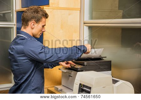 Young Man Operating Photocopier Machine