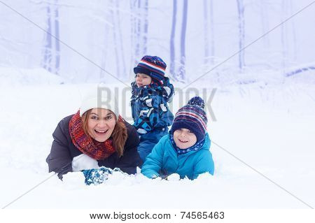 Happy Mother And Her Two Little Kid Sons Playing With Snow