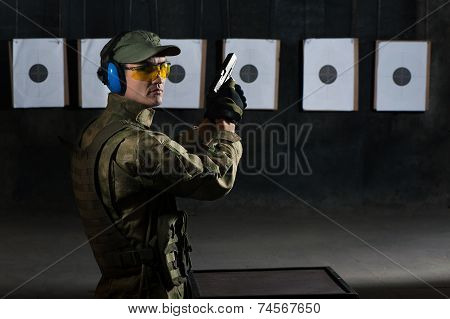 Man shooting with rifle at a target in shooting range
