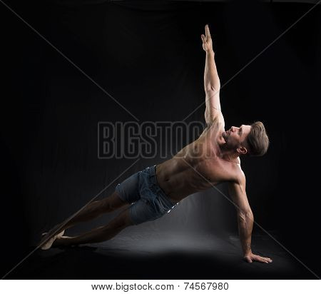 Young Sexy Shirtless Man Stretching On The Floor