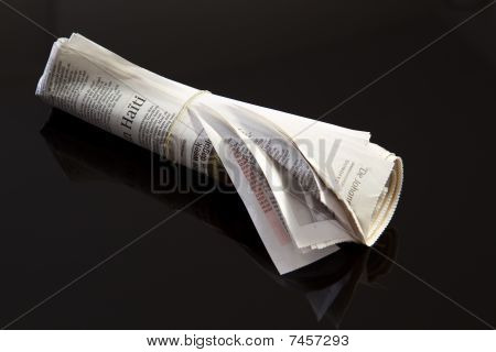 Rolled Up Newspaper On Black