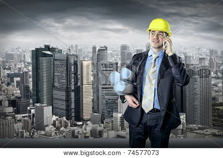 Architect in protective helmet speaking by phone