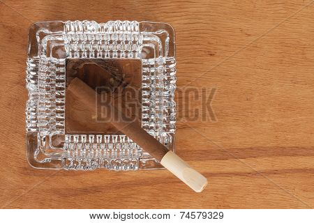 Glass Ashtray With Cigar Stands On A Wooden Surface