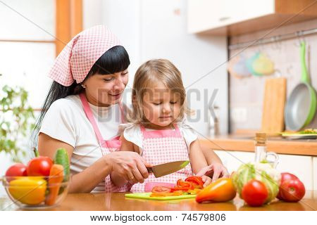 mother and kid girl cook and cut vegetables on kitchen