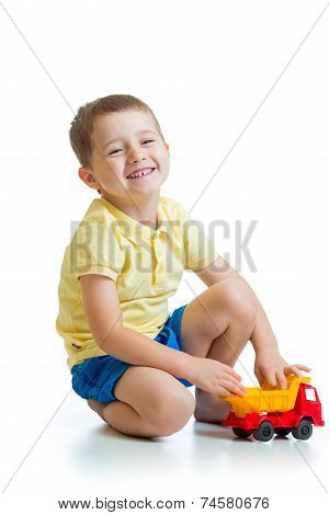 funny kid playing with lorry toy isolated on white