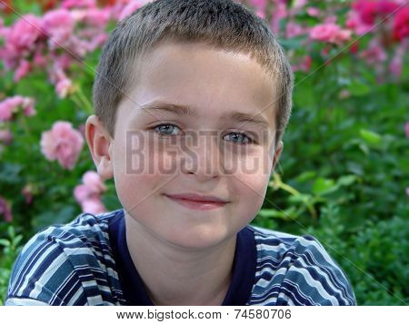 ten year old boy smiling on the background of the flowers
