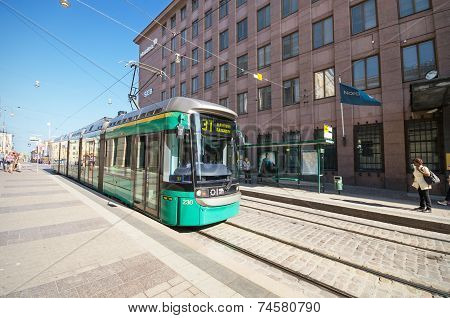 A tram is arriving to a station at the commercial district of Helsinki.