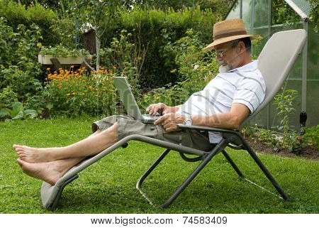 senior  in garden at leisure with laptop computer