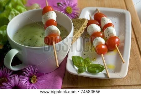 Basil soup with salad of fresh bocconcini mozzarella and cherry tomatos on skewers