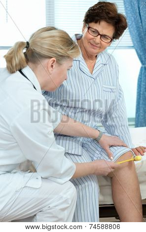 Physician checking reflexes of a senior  woman in hospital