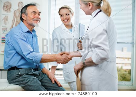 doctor shakes hands with a senior patient