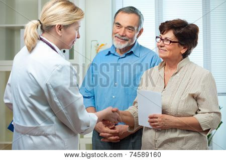 doctor handshaking with a senior couple