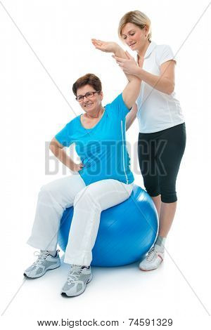 Senior woman doing fitness exercise with help of trainer at sport gym