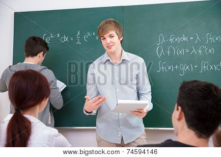 High school students discussing homework in front of the blackboard