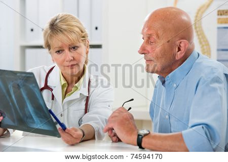 Doctor explaining x-ray results to senior patient