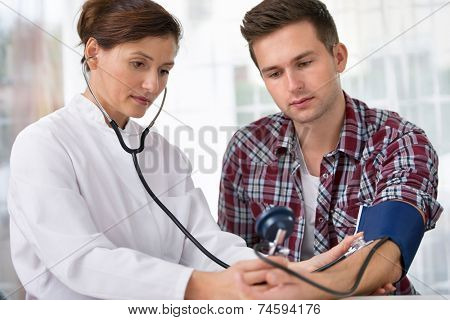 Female doctor checking young man blood pressure