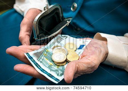 elderly caucasian woman counting money in her hands