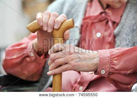 Hands of the old woman with a cane