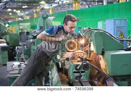 Young turner adjusts machine