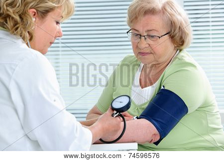 Doctor measuring blood pressure of senior patient