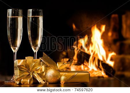 two glasses and gift boxes  in front of fireplace