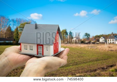 Hands holding a house model against building ground background