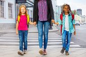 stock photo of grown up  - Two kids with woman safely walking over the crossing on the street holding grown - JPG