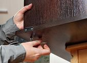 picture of key  - Assembling of furniture with a hexagon furniture key in hand of the master - JPG