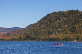 pic of canoe boat man  - A man canoeing in a lake during the fall in Canada