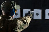 stock photo of shooting-range  - Man shooting with gun at a target in shooting range - JPG