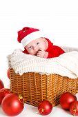 picture of new years baby  - Cute newborn baby wearing Santa Claus hat sleeping in basket - JPG