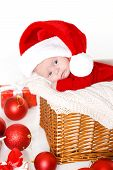 stock photo of new years baby  - Cute newborn baby wearing Santa Claus hat sleeping in basket - JPG
