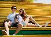 stock photo of bench  - Young modern stylish hipsters couple rest in bench city park sunny portrait couple teenagers in love summer - JPG