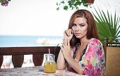 foto of woman red blouse  - Attractive red hair young woman with bright colored blouse drinking lemonade on a terrace - JPG