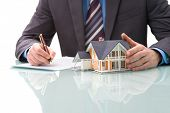 stock photo of confirmation  - Man signs purchase agreement for a  house - JPG